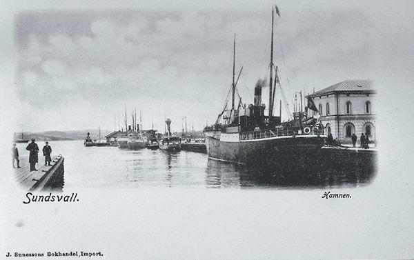 """Hamnen med ångfartyg. Till höger syns en del av Tullpackhuset. Brevkort. Bildtext """"Sundsvall. Hamnen J. Sunessons Bokhandel. Import""""."""
