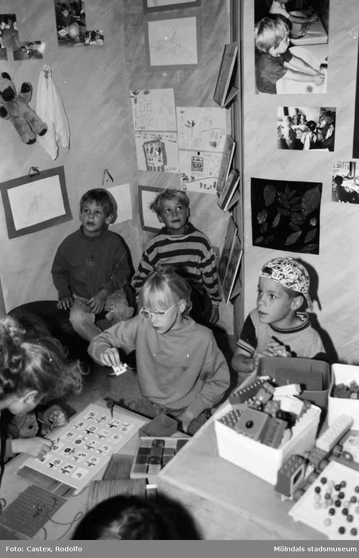 Barn som sitter på golvet och gör olika aktiviteter. Utställningsvernissage av och om Katrinebergs daghem på Mölndals museum 1993-09-10.