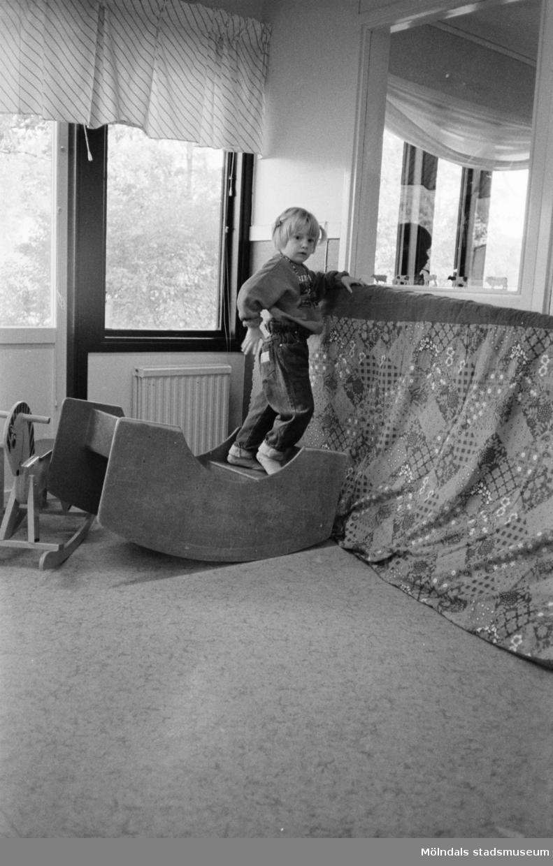 Inomhus på Katrinebergs daghem. Ett barn står på en trägunga och lutar sig mot en stående mjuk madrass som är överdragen med ett tyg. I bakgrunden syns en gunghäst samt fönster med gardiner.
