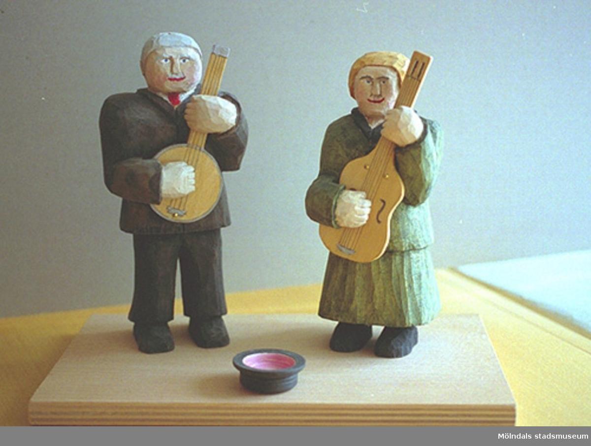 """En kvinna och en man står och spelar gitarr. Framför dem på marken ligger en upp-och-ner-vänd hatt. Harry Bergmans """"gubbar"""" (träfigurer)."""