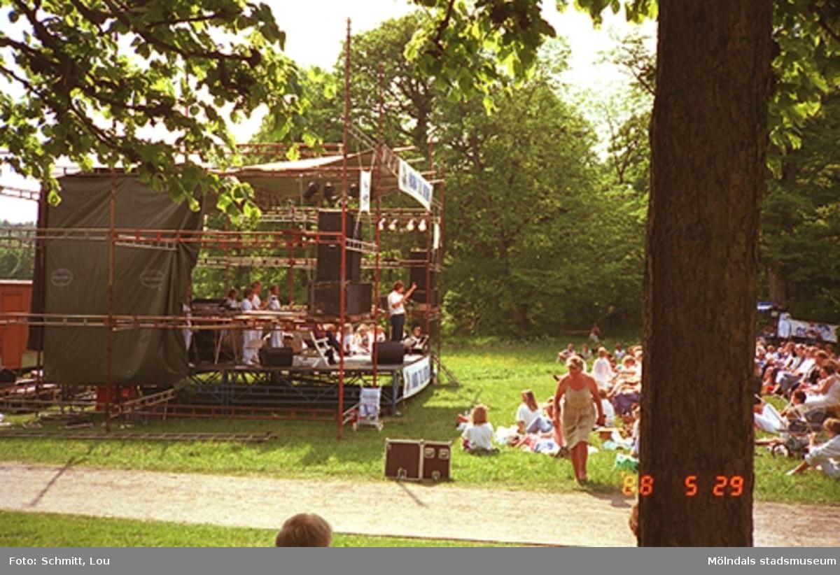 Människor sitter på gräset och lyssnar till Lasse Berghagen, som sjunger på en tillfälligt uppbygd scen på Gunnebo slotts baksida, 29 maj 1988.