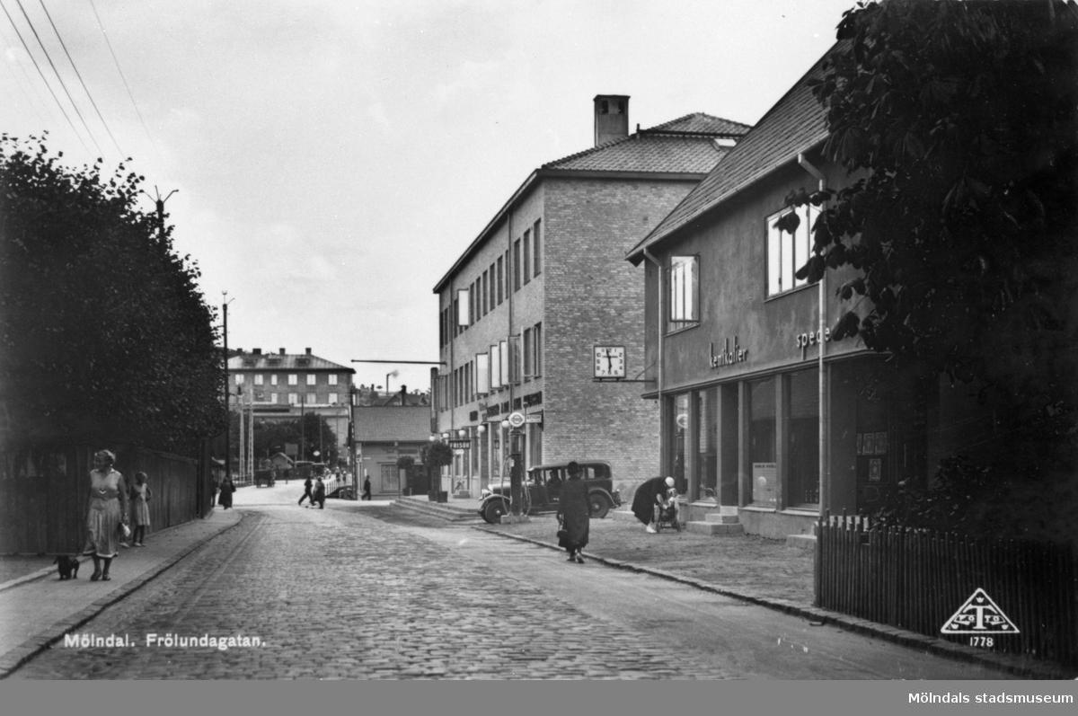 """Vykort """"Mölndal. Frölundagatan"""" mot Mölndalsbro, 1940-tal. Till höger ser man Frölundagatan 3 och 1. I bakgrundens mitt ses den höga byggnaden Röda Kvarn (biograf på Kvarnbygatan 1)."""