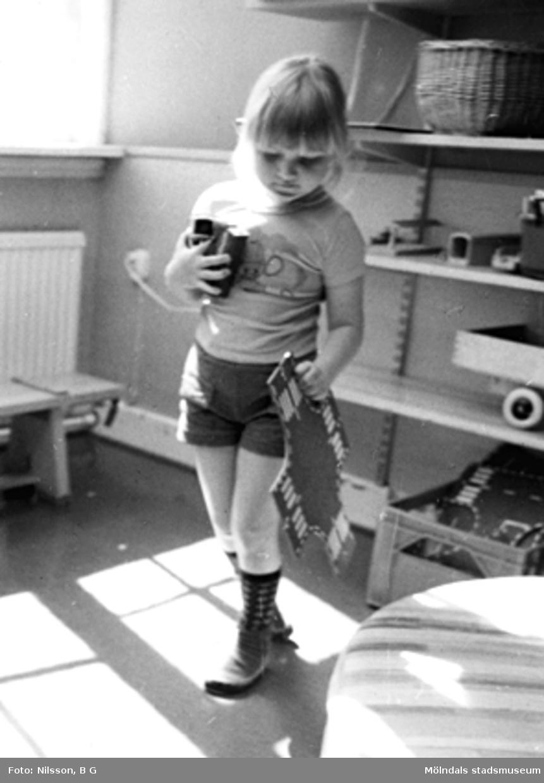 En flicka som håller leksaker i sina händer. Holtermanska daghemmet, okänt årtal.