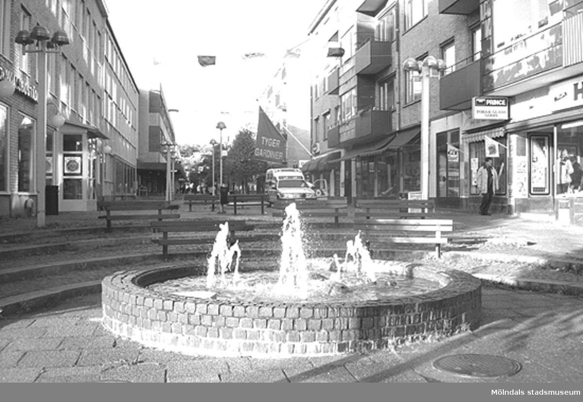 Fontänen i början av Brogatan. Mölndalsbro i dag - ett skolpedagogiskt dokumentationsprojekt på Mölndals museum under oktober 1996. 1996_1061-1076 är gjorda av högstadieelever från Kvarnbyskolan 9C, grupp 3. Se även 1996_0913-0940, gruppbilder på klasserna 1996_1382-1405 samt bilder från den färdiga utställningen 1996_1358-1381.