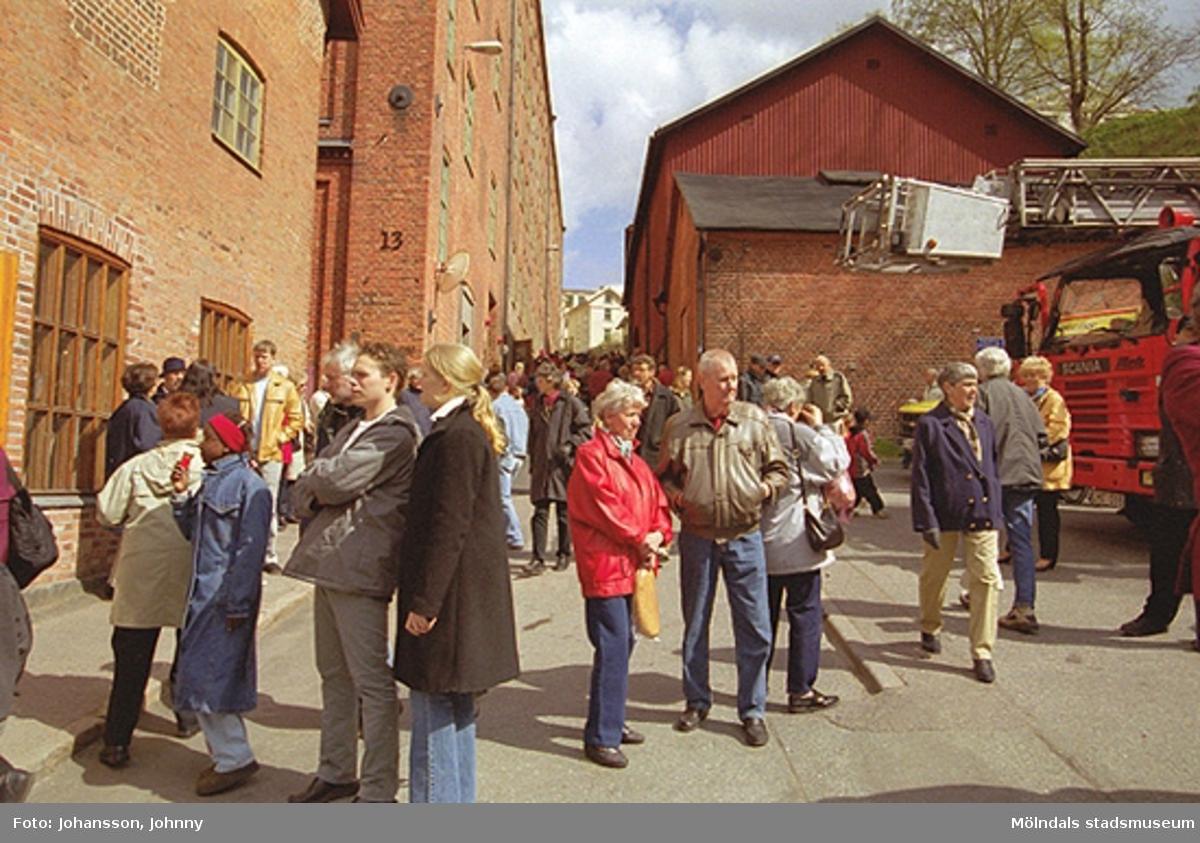 Besökare står utanför Nymans kvarn på Götaforsliden. Till höger ses Hem- och hushållsmuseet/Lantbruksmuseet (Mölndals hembygdsförening).