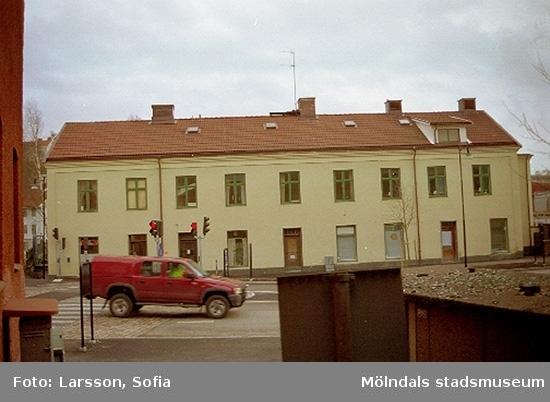 Byggnad 213 på Kvarnbygatan 4. Framför byggnaden kör en röd bil kör åt Mölndals Bro.