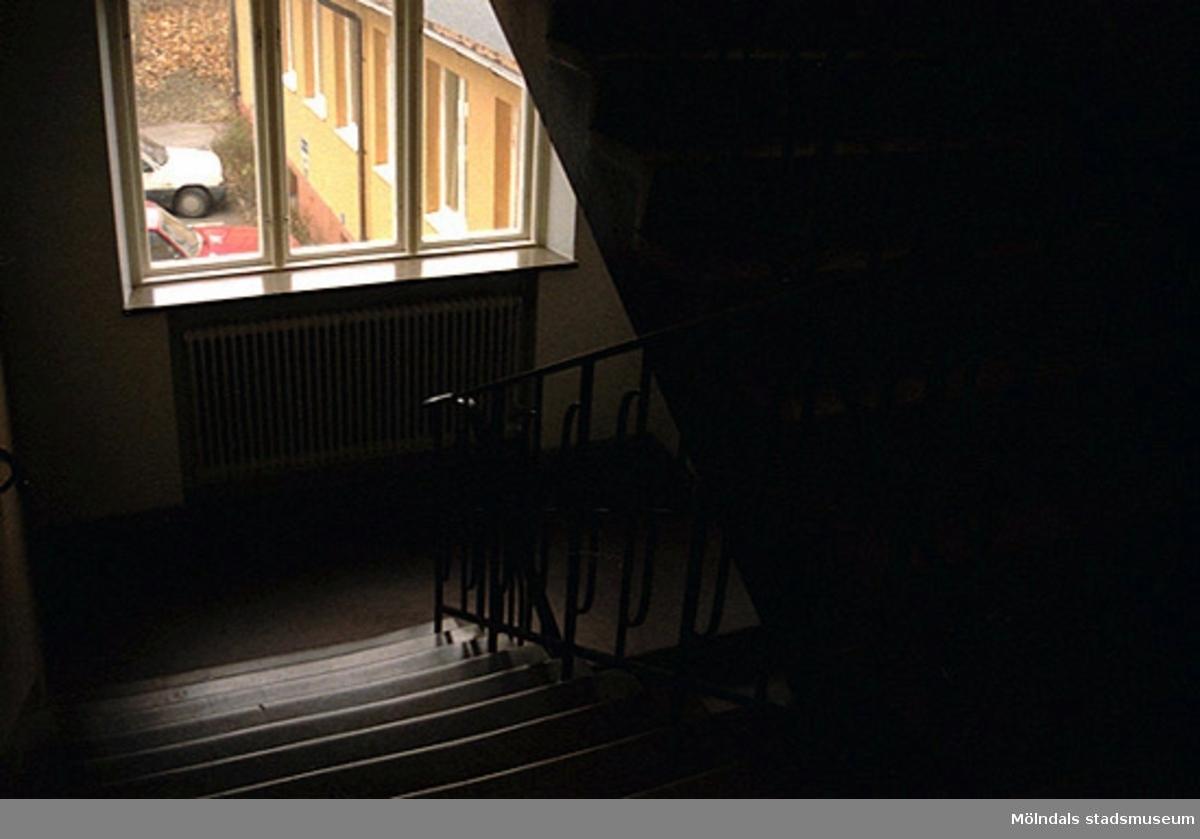 Byggnadsdokumentation av Häradsgatan 1. Vy inifrån trappuppgång, ut genom ett fönster, tillhörande ett bostadshus. Huset var elevbostad till verkstadsskolan/yrkesskolan på Terrakottagatan. Blev senare kontor. Relaterade motiv: 2002_0910 - 0917. Oktober 1998 - januari 1999.
