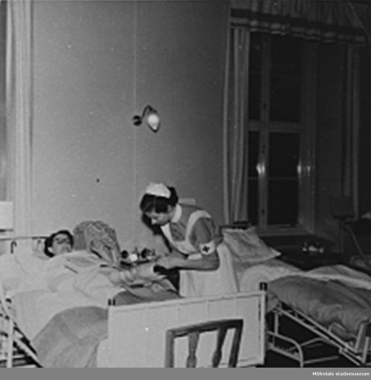 """En sköterska tar hand om en patient på Sabbatsbergs sjukhus i Stockholm, cirka 1958. Det var viktigt att ha uppkavlade ärmar vid beröring av patient.Vid 18 års ålder fick man börja på Svenska Röda Korsets sjuksköterskeutbildning. Då blev eleven antagen till 3 månaders provtjänstgöring den s.k """"plättperioden"""". Under denna tid användes en liten mössa till arbetsuniformen som man fick vid utbildningens början. Den lilla mössan avvek från den ordinarie mössan för att visa att eleven gick på prov. Efter provtjänstgöringen fick eleven veta om hon godkändes för vidare utbildning på 3,5år. Efter 2 års studier fick eleven bära den vita armbindeln och blev därmed undersköterska.Arbetsuniformen var skräddarsydd och bestod av en blå bomullsklänning, ett vitt förkläde som knäpptes i kors i linningen med särskilda manschettknappar och en vit mössa. Klänningens längd skulle vara ett visst antal centimeter ovanför golvet och förklädet skulle vara ett visst antal centrimeter ovanför den nedersta klänningsfållen. Man fick endast använda svarta strumpor och svarta skor eller bruna strumpor och bruna skor till klänningen.Till klänningen hörde också en vit krage till som fastsattes med knapp baktill och  med sjuksköterskebroschen framtill. Till klänningen fanns ett särskilt bälte som gjorde att förklädet inte skulle vika sig i midjan. På vänster ärm fastsattes den vita armbindeln som visade att det var en Röda Kors syster! Den vita mössan var enligt ett mönster särskilt för Röda Korsets sjuksköterskor (varje sjuksköterskeskola hade sin egna design av mössan). Endast nålar med pärlhuvud fick användas på mössan. På mössan fästes hakrosetten. Vid utomhusvistelse fick man bära den tillhörande svarta kappan. Den skulle vara längre än klänningen. Till kappan var man tvungen att använda svarta strumpor och svarta skor och sätta fast den vita armbindeln på vänster ärm. Man använde också en särskild mössa med hakband den s.k Kapotten. Det fanns också en tillhörande frack till uniformen som bara """