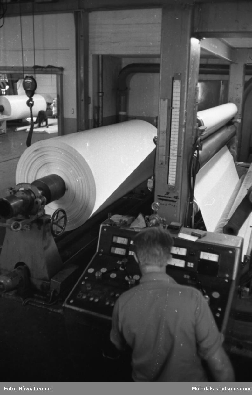 Mannen på bilden är arbetsledare Lars Elfström i arbete vid maskin, RM 5. I bakgrunden syns maskin Glätt 5. Papyrus i Mölndal, hösten 1970.