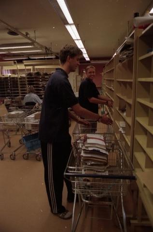 Posttjänstemän sorterar post inne i sorteringsdelen på en postanstalt. Tillhör en dokumentation av en lantbrevbärare i trakten av Valdermarsvik av fotograf Ove Kaneberg.