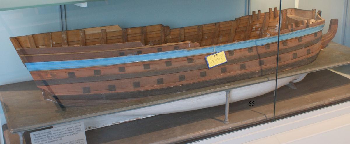 Fartygsmodell 60-kanonskeppet Prins Carl, skrovmodell. Bordläggningen limmad på gavlar, utan inredning, galjon och akterspegel. Modellen är brunmålad upptill med blå rand och svarta kanonportar. Under vattenlinjen vitmålad.