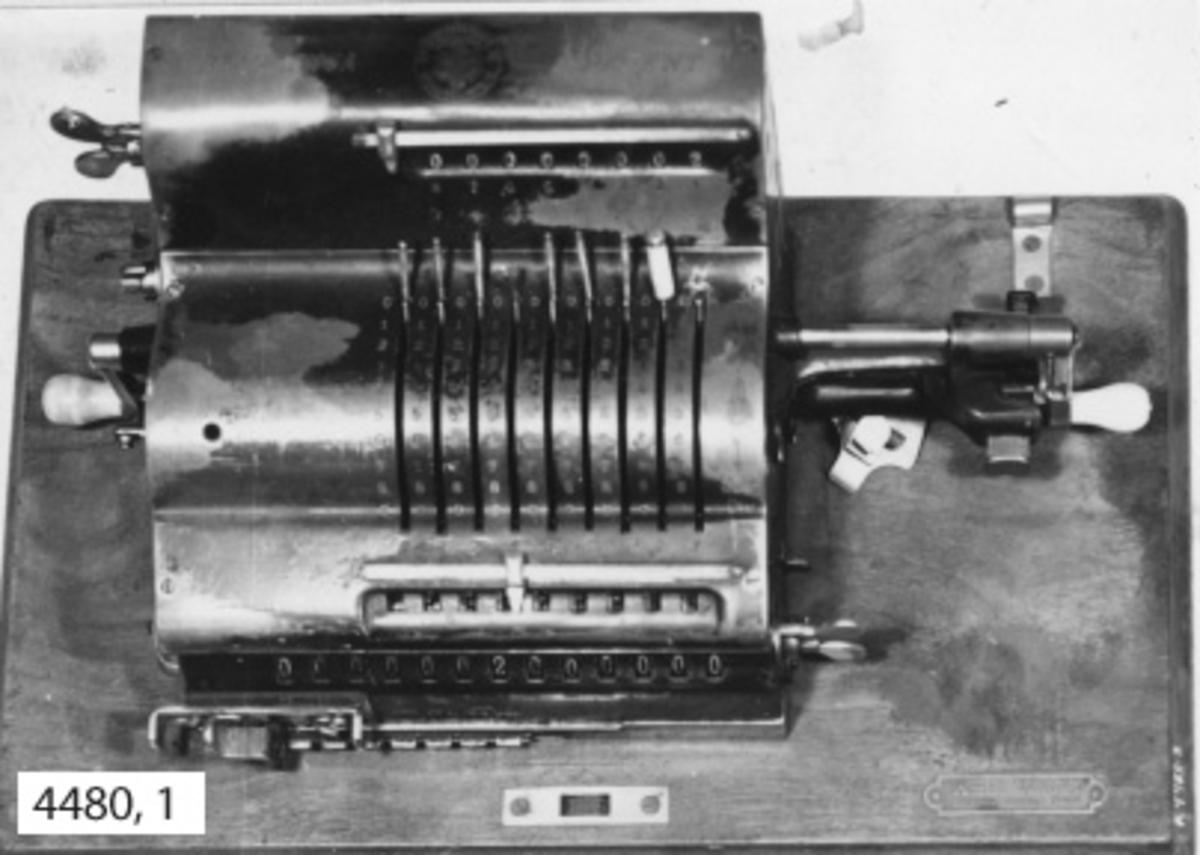 Räknemaskin av märket Brunsviga. Fabrikatet är tyskt och troligen från början av 1900-talet. Maskinen kan användas för addition, multiplikation, subtraktion och division. Den är fastsatt vid en platta av trä. Över maskinen en skyddskåpa av bleckplåt, svartlackerad och med bärhandtag av läder. Den fastlåses vid träplattan. Märkt i gult: Brunsviga Patent samt i rund stämpel: Grimme Natalis CG. Auf Actien Brunschweig med emblem och två drakar.