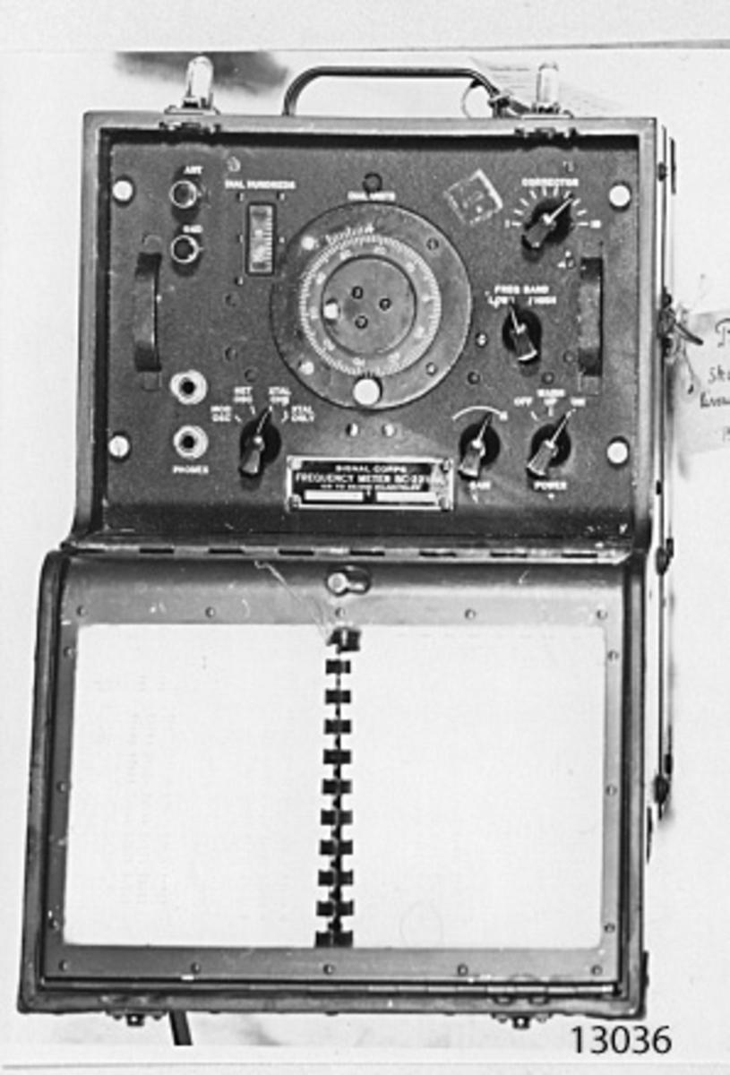 I låda av trä, mörkgrön, med på ena sidan lock och innanför detta panelen med rattar och jack för telefon m.m. På lockets innersida, anvisningar och kalibreringstabeller. Märkning på panelen: Signal corps Friquency emter BC-221-AL 125 to 20.000 Kilocycles. 12085: CZR 34542 PHILA.43. Bruksanvisning (i blå pärm) finns i museets bibliotek.