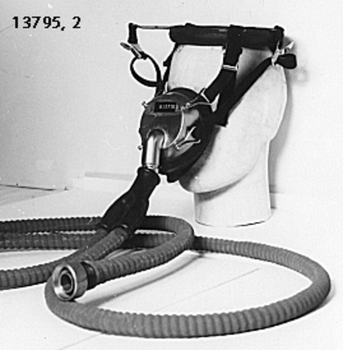 Till munstycket är två stycken slangar kopplade, vilka anslutes till en pulmotor. Munstycket hålles på plats med fyra remmar av tyg, vilka fästes på en ring som placeras på huvudet. Märkning: Dräger.