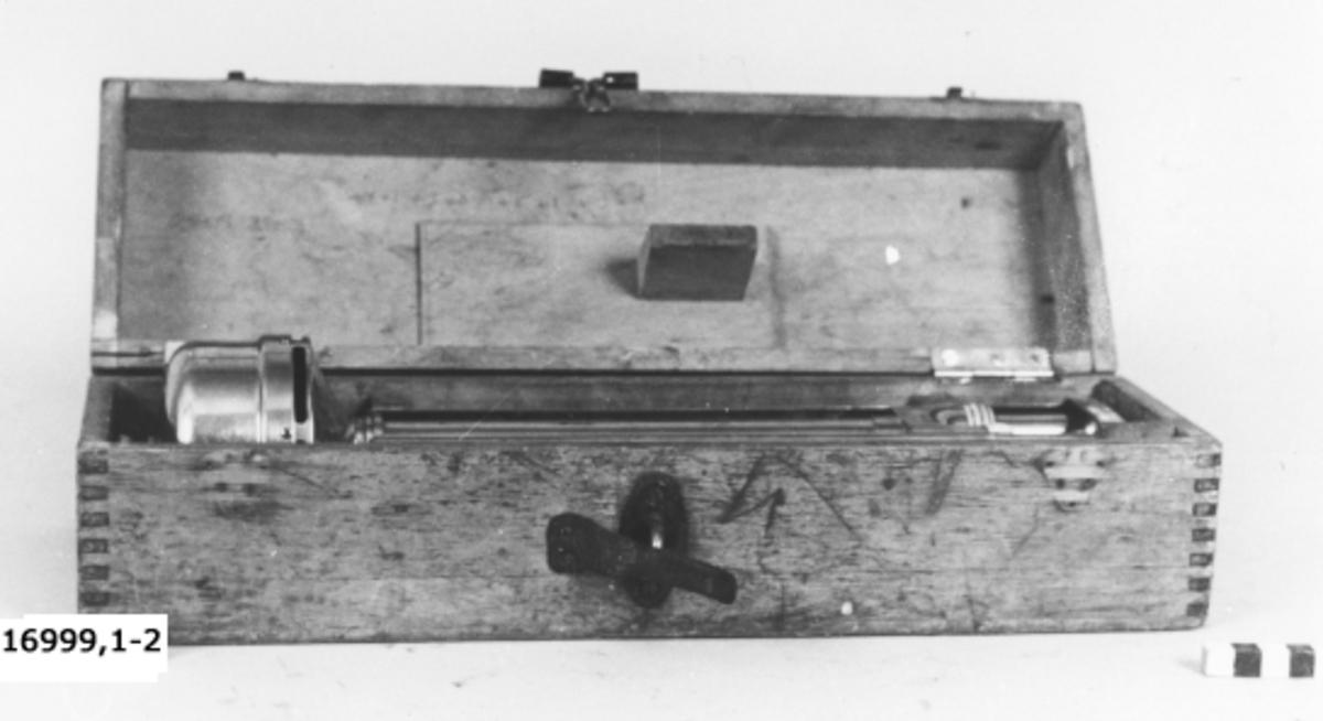 """Instrument bestående av två termometrar, graderade från -30_C till +40_C. Termometrarna är fästa bredvid varandra i öppna metallhylsor. Mellan dem ett rör som står i förbindelse med den cylinderformade dosan överst. Dosan innehåller en fläkt som bringas i rörelse genom uppvridning med nyckel. Termometrarna märkta på baksidan= """"Wihl Lambrecht, Göttingen"""". Upphängs med lina fäst i kopparkrok."""