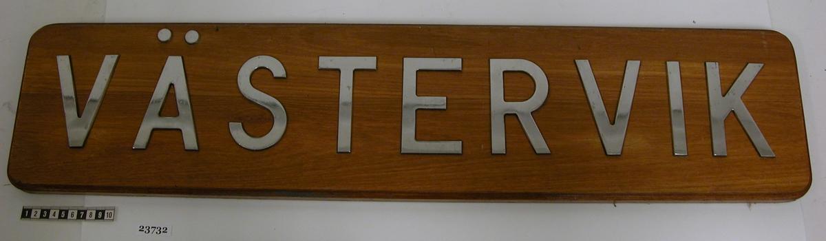 """Rektangulär, fernissad träplatta med rundade hörn och falsad kant. På brädan sitter bokstäver av putsat, rostfritt stål fastskruvade. Bokstäverna bildar texten """"VÄSTERVIK"""". Bokstävernas höjd är 100 mm."""