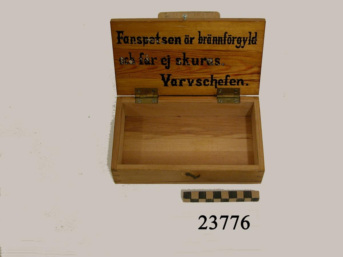 """Träskrin med lock och gångjärn av mässing  med kronostämplar. Skrinet låses med liten hasp. På lockets insida tryckt text : """" Fanspetsen är brännförgyld och får ej skuras. Varvschefen """". Anmärkning: I skrinet förvaras MM 23774, MM 23775."""