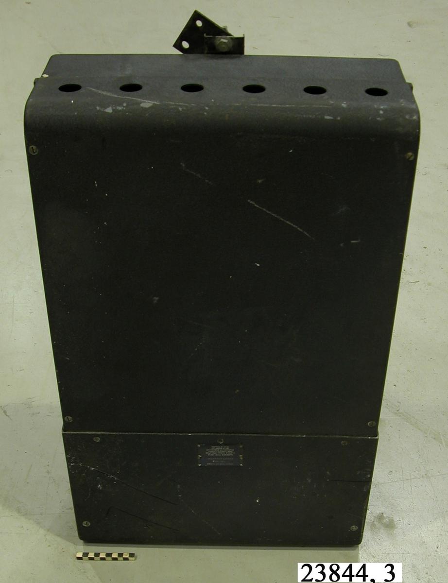 """Rektangulär metallbox, lackerad i svart med """"krympfärg"""". Boxen har en öppningsbar lucka på framsidan. På ovansidan finns sex cirkulära ventilationshål. På undersidan finns två stötdämpande fötter. Mottagaren innehåller en antennmotor. För vidare information se """"Handbok för radar PN-58"""", Decca Navigator och Radar AB, fastställd av Kungliga Marinförvaltningen 23 augusti 1956. Handboken finns i Marinmuseums arkiv."""