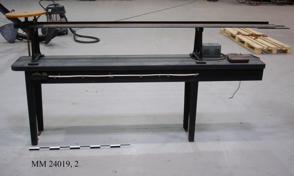 """Bänken är delad i två delar och utförd i svartmålad trä. Eluttag och strömbrytare finns på båda sidorna. En räls på stålställning finns ovanpå bänken. I ena änden av rälsen finns en rund platform för placering av en lanterna. Platformen är höj- och sänkbara och kan även """"tippas"""" via reglage. På rälsen finns en mätskala från 0,1 till 1. I övrigt kan bänken bultas fast i golvet. På bänken finns också en mindre transformator monterad. Den är tillverkad av Tufvassons Transformatorfarbrik i Sigtuna. Strax intill transformatorn är bänken märkt med tre klisterlappar med dynamotext. En röd tejpbit med texten: """"RÖTT LJUS 62"""". En svart tejpbit märkt med texten: """"VITT LJUS 54"""". En grön tejpbit märkt med texten: """"GRÖNT LJUS 60"""". Se även MM 24019, 1."""