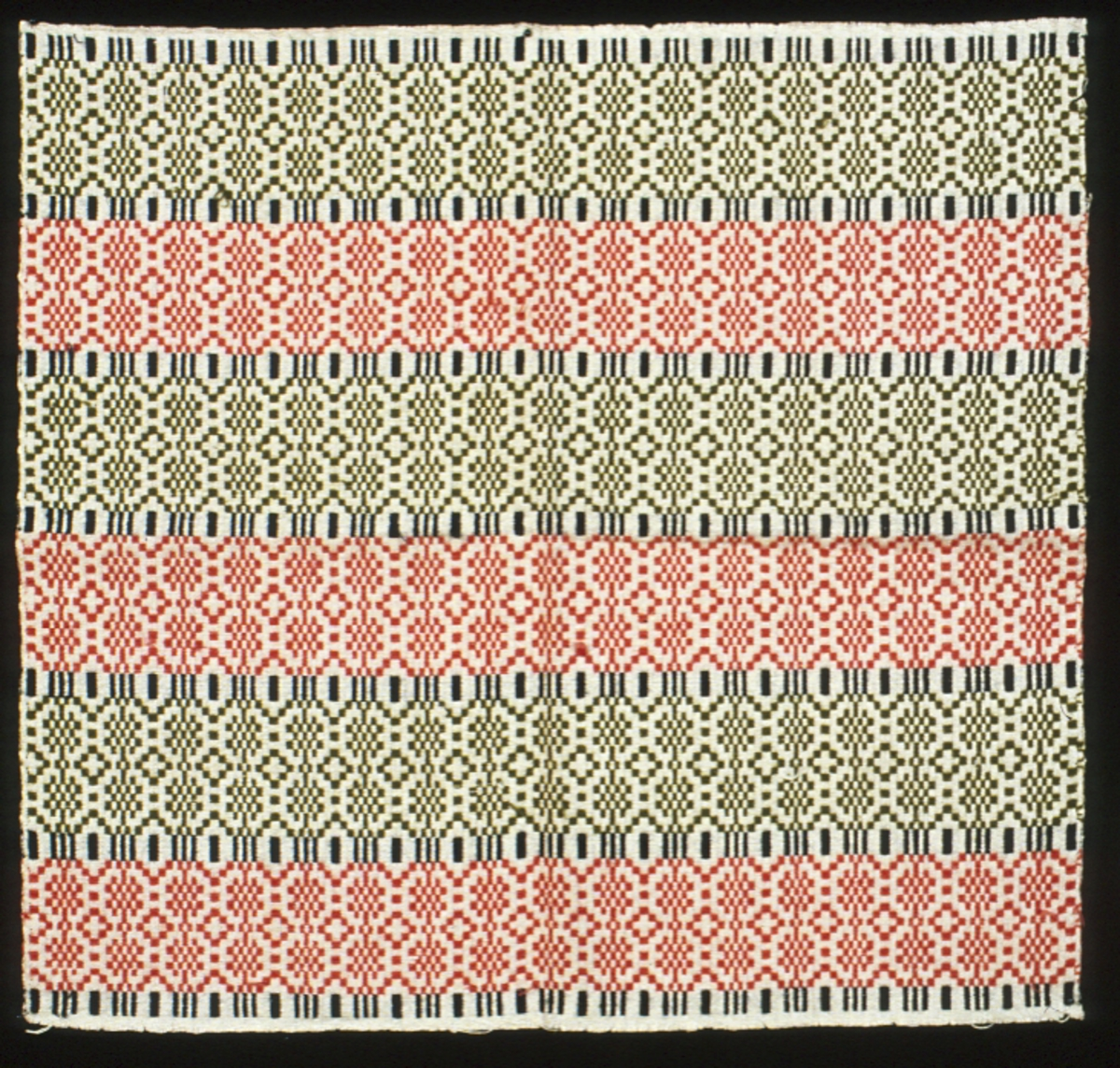 """Vävprov i opphämta. Yttäckande bottenmönster som blir tvärrandigt i färgerna rosa och grönt samt smala avdelade ränder i mörkblått på botten av halvblekt lingarn. Stadkanter i två sidor, kastad i två sidor. Varp i halvblekt 1-trådigt lingarn, 14 trådar/cm. Botteninslag samma som varpgarnet, 8 trådar/cm, ett botteninslag mellan varje mönsterinslag. Mönsterinslag i kulört 1-trådigt ullgarn, två trådar tillsammans. Vidhängande etikett med handskriven text: """"Profväfnaden N° 14""""."""