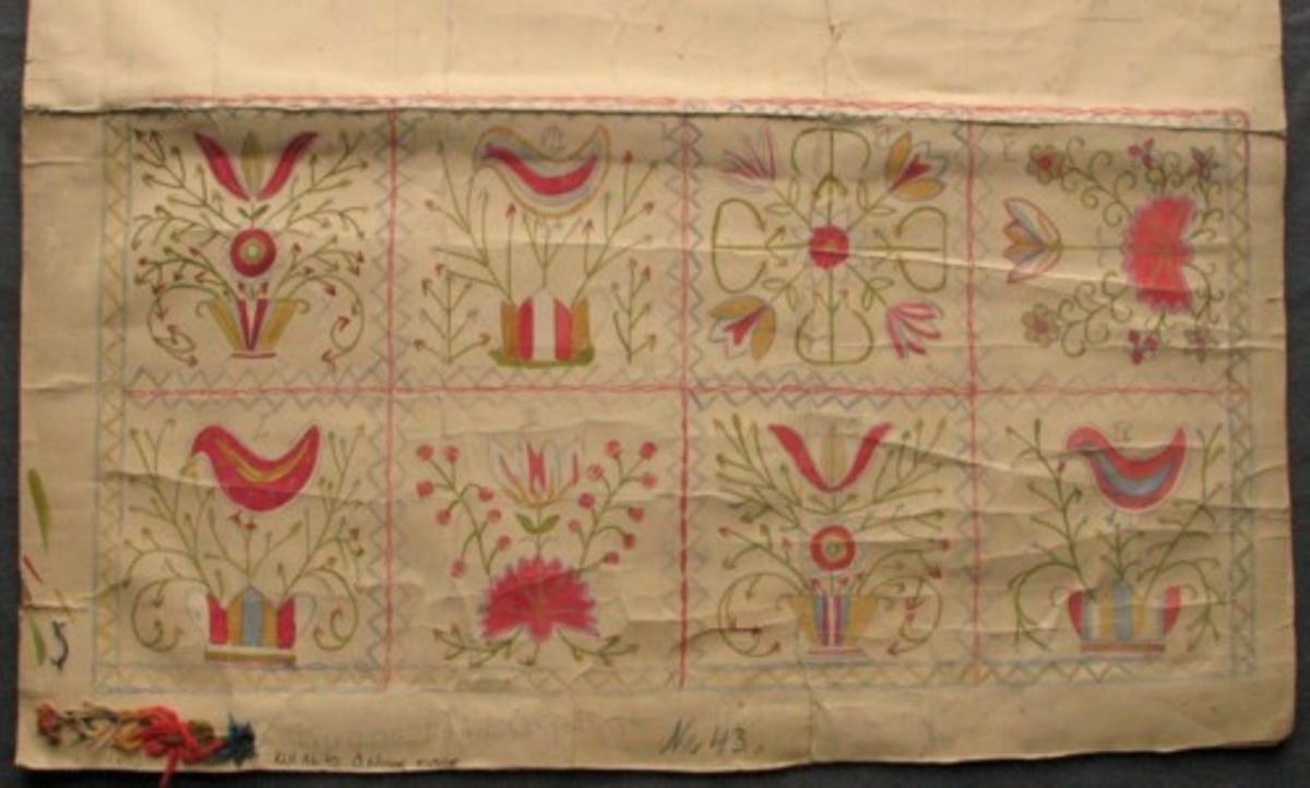 """Skiss målad på styvare papper. Del av kudde. Kudden är broderad i rutor som är indelade med en zick-zackbård. En del av mönstren i rutorna är återkommande. Olika vaser med buketter, kvistar med fåglar och blomkvistar i mörlrosa, ljusblått, gulbeige och grönt. Garnförslag är monterat i kanten. Gammal märkning: """"kudde från Östra Göinge, Nr 43."""""""