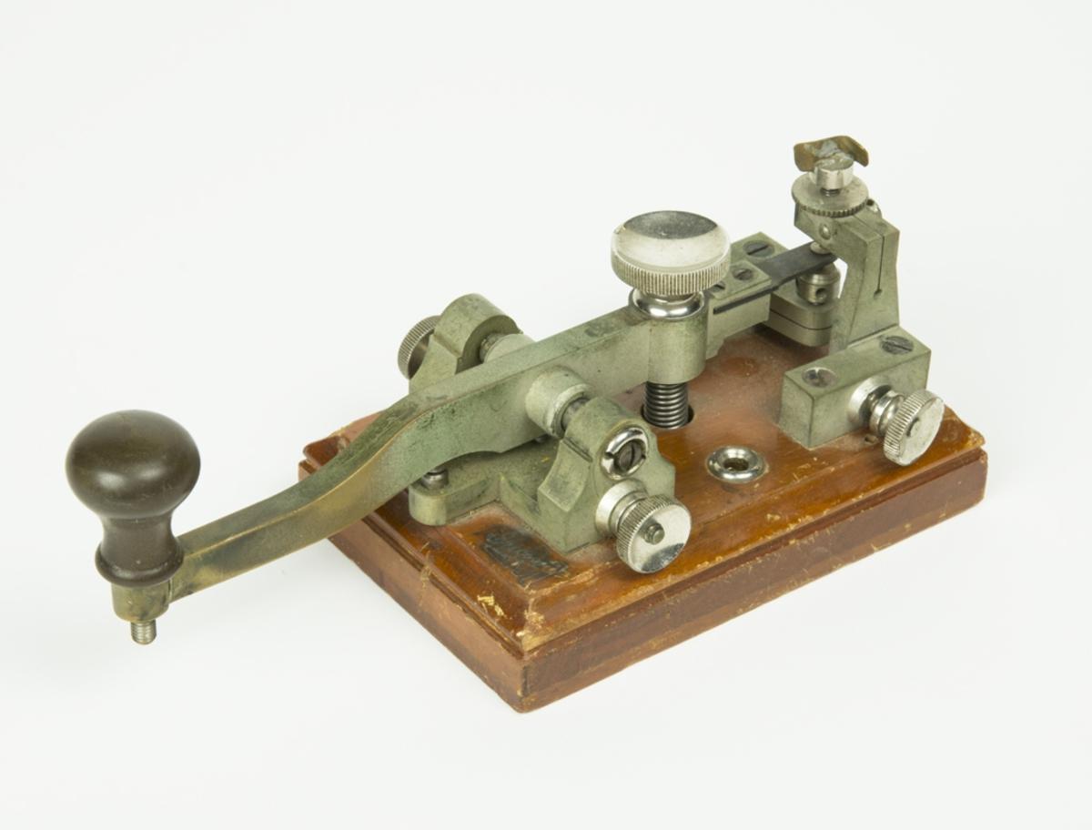 Telegrafnyckel monterad på träplatta.