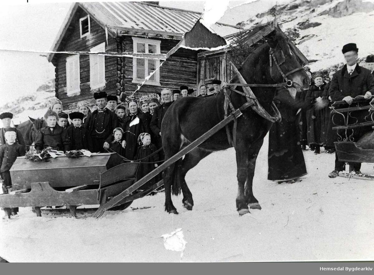 Frå graveferda etter Birgit Dokken i 1909, fødd Ro i Gol. Ola, mannen til Birgit, står ved kista og held taumane. Like ved kista er dottera, Jørgine. Heilt til høgre står Asle Ellingplass og held i sluffa.