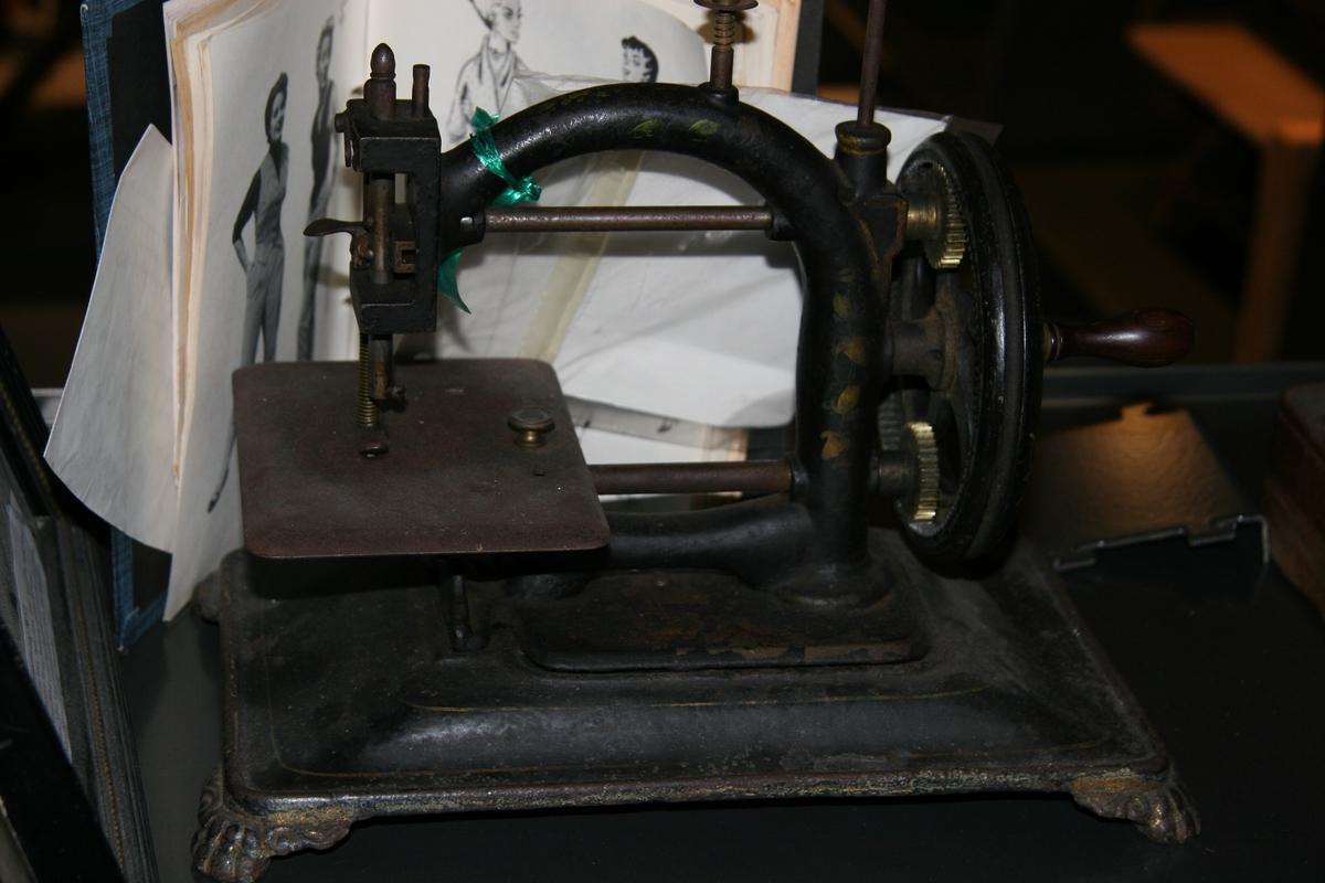Symaskinen har hverken skyttel eller sp ole. Vanskelig å si bestemt alder, men antakelig fra ca. 1850. Ragna Tjomsland født Bergstøl hadde denne maskinen fra sitt hjem. Det fortelles at Berte Seland drev som skredder og sydde som mannfolksskredder. Hun var stemor til Ragna Tjomsland.