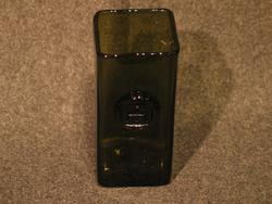Kvadratisk bunn, rett mage. Påsatt medaljong på en side i øvre halvdel, med stemplet monogram. Motiv: Byport i Gamlebyen. Mørk grønn farge.