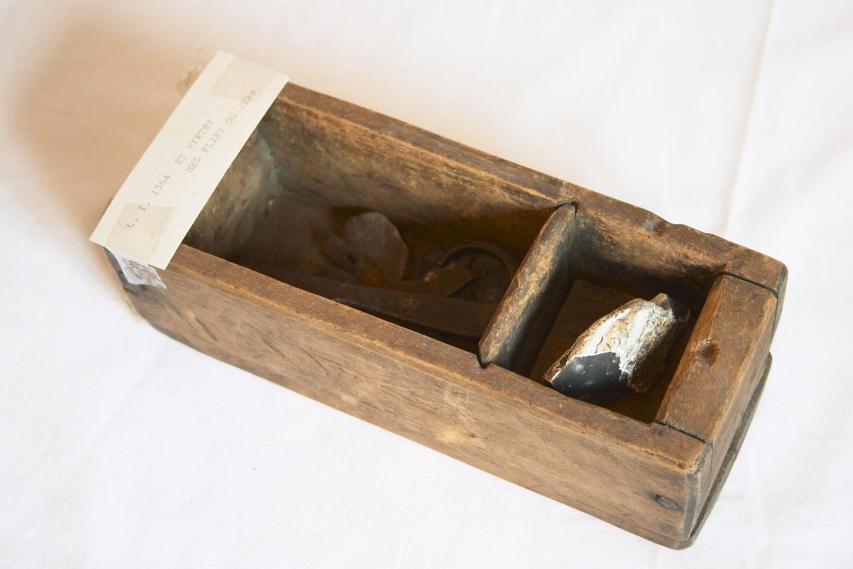 Lagt i en skuff med 2 rom. En skuff laget av tre, ufarget. Denne skuffen har to rom hvor det finnes flintsteiner og to jern. Det ene er formet med en krok nederst, det andre er en del av et jernstykke. Flintesteiner og tønder samt jern ble brukt før fyrstikkens tid for å få fyr.