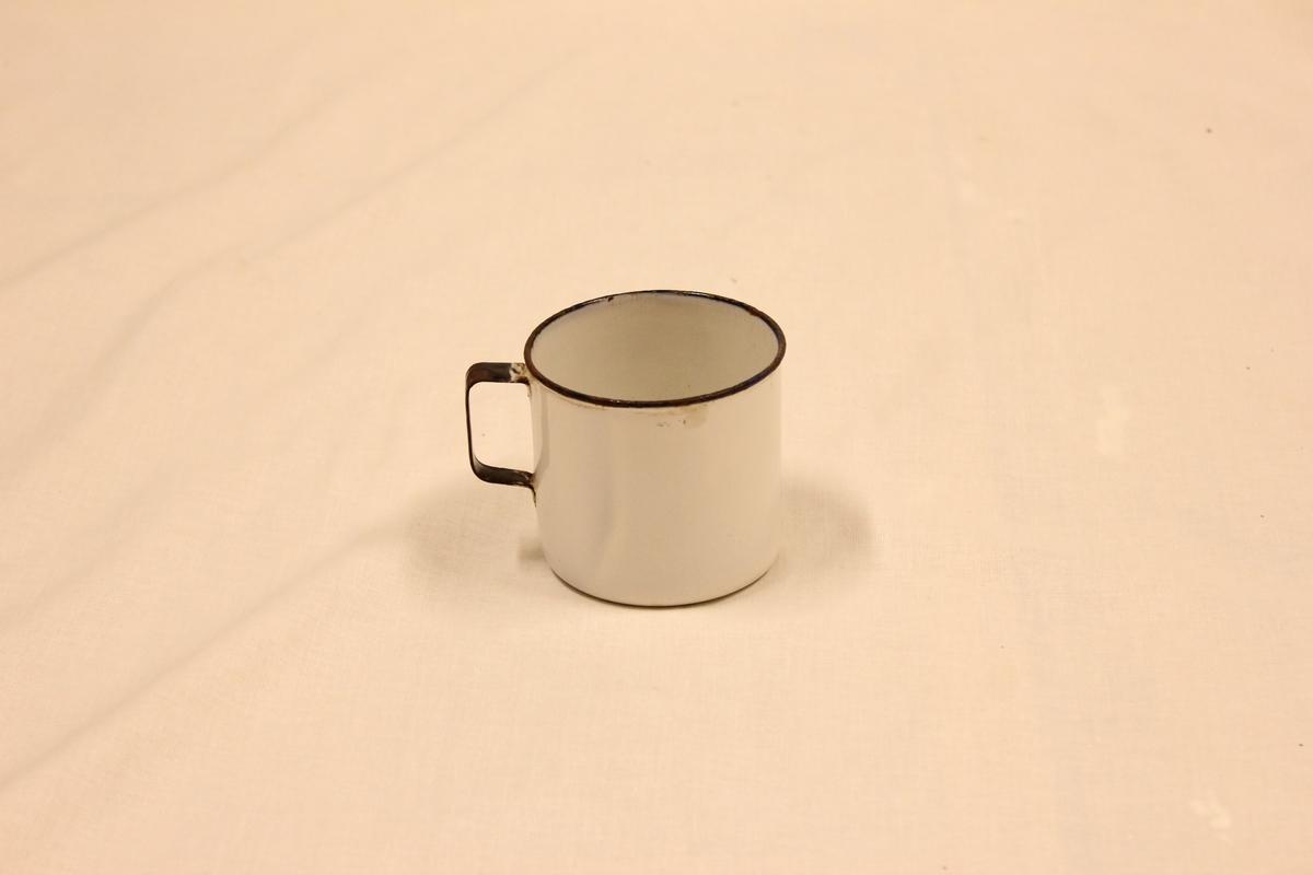 Hvitt blikk kopp med sort markering på håndtak og rundt åpningen oppe.