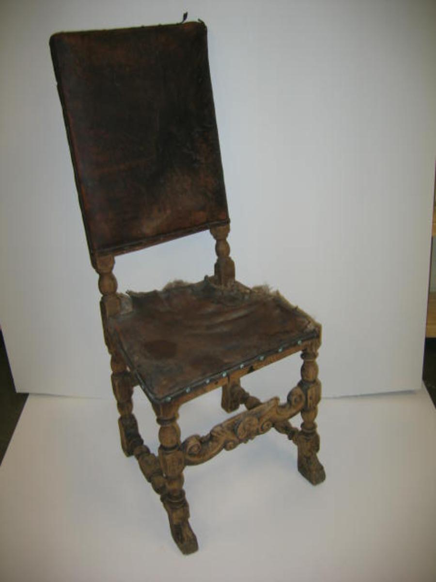 """1 stol.  Høirygget stol av ask av samme type som """"Bænk og stol i Norge""""  fig. 188. Fra ca. 1660. Sæte og ryg betrukket med skind, noget defekt. Forbindings bret i barok. Gave fra Simon og Lars Smidji, Feios."""