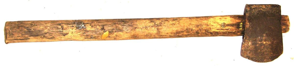 """1 navöks.  Liten navöks av """"paddetypen"""", se no 5197, hvor den i midten av forrige aarhundrede fra Amerika indförte öks er tat som model. Nærværende eksemplar er hjemmesmidd og bruktes her i Sogn og i Valdres jevnlig hjemmesmidde ökser av denne typen.  Med navöks forstaaes en liten haandöks, hvormed man under lövhugst, naar store trær skal löves klöv op i toppen og hugget """"navet"""" grenene ned. Disse blev senere smaahugget til kjerver med snidel.  Øksen er meget slidt. Eggens bredde er 7,4 cm, længde med skaft 45,7 cm.  Gave fra Øystein Larsen Klævold, Kirkebö."""