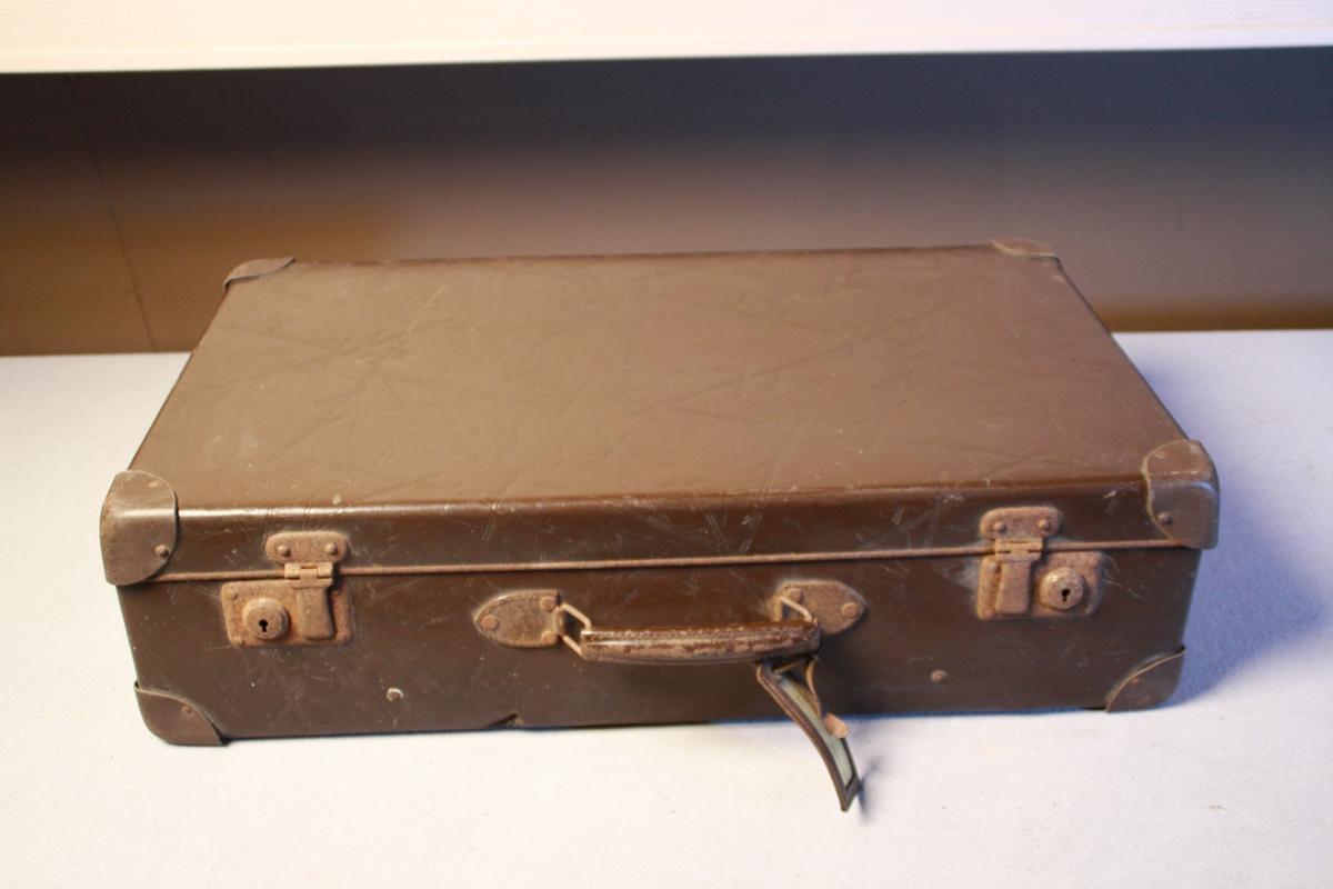 Koffert i vulkan fiber. Forsterka hjørner i metall, handtak og to låser. Sett saman med naglar. Trekt med mønstrete papir inni. Festestroppar. Adresselapp.