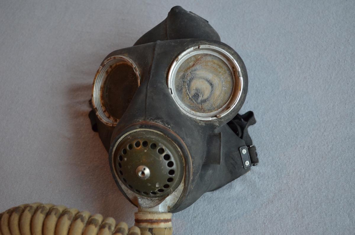 Gassmaske med slange ned til beholder i metall. Gummien er noko morkent og plastglasa er sprukkne. Metallbeholder er litt rusta.