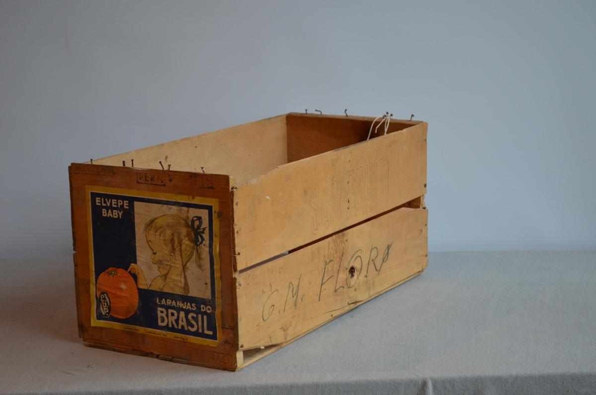 Enkel fruktkasse. Noko øydelagt. Har truleg frakta apelsiner frå Brasil. Mange stempel både inni og utanpå kassa. Eine sida har side med logo limt på.