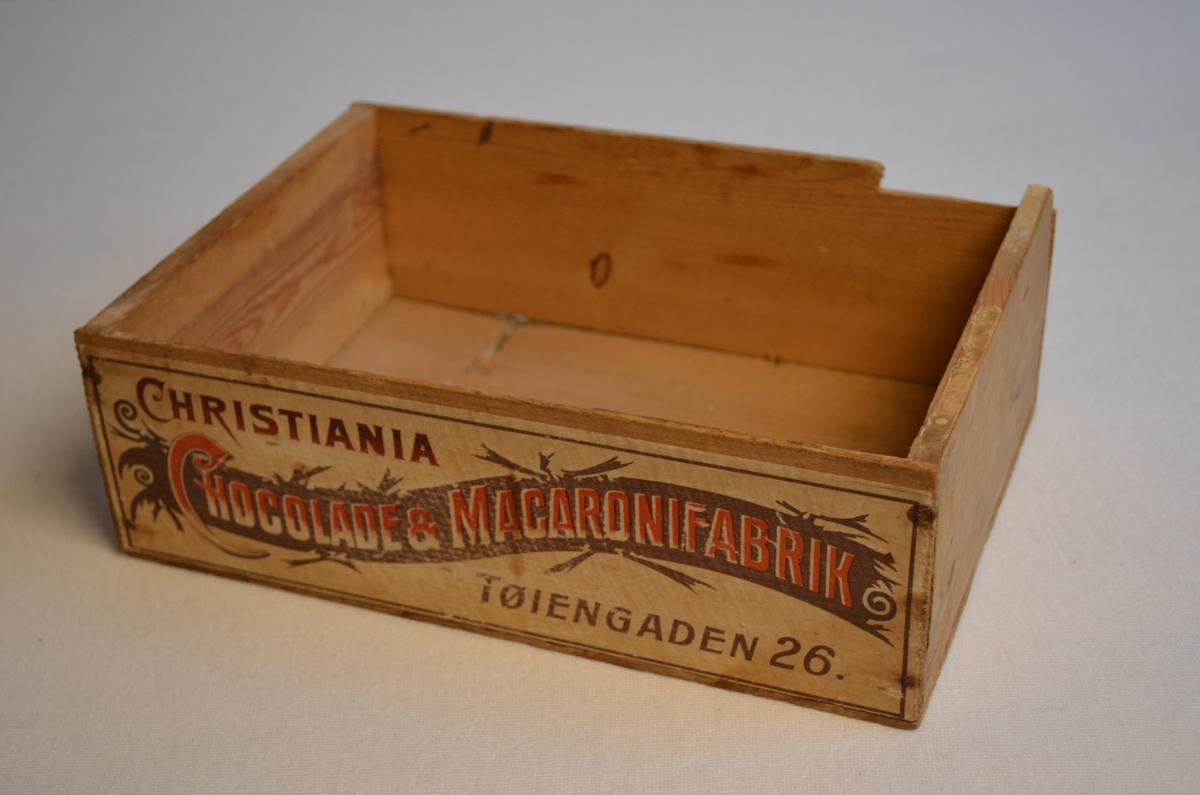 Lita trekasse utan lok som opprinnelig kom frå ein sjokolade og makaronifabrikk i Oslo. Ein del av kanten på kassa er broten av. Logoen på kassa er i raudt og brunt.
