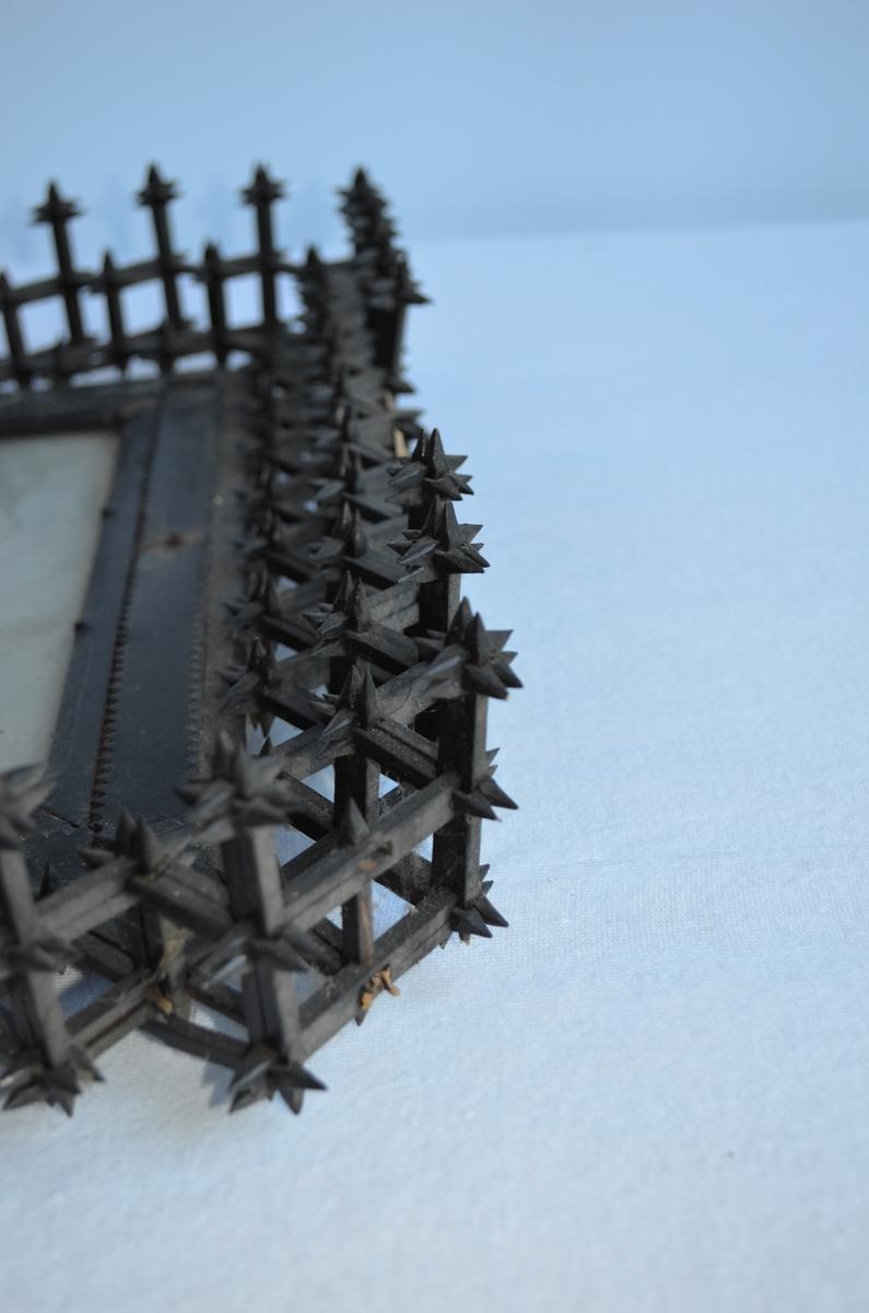 Bilderamme laga av skråtobakkspinner som er satt saman og festa til sjølve ramma. Vanleg tidsfordriv for sjømenn å lage ting av skråtobakkspinner. Det vart nemnd for frivaktsarbeid og det er vanleg å finne slike rammer langs norskekysten.