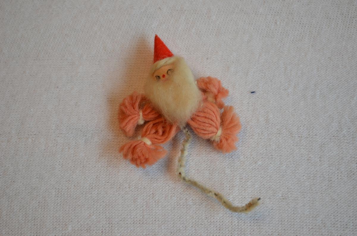 4 Julenissar laga av tråd med papp haude og skjegg av bomull. Raudfargen på tråden er falma. Nissane ser ut som dei spring.