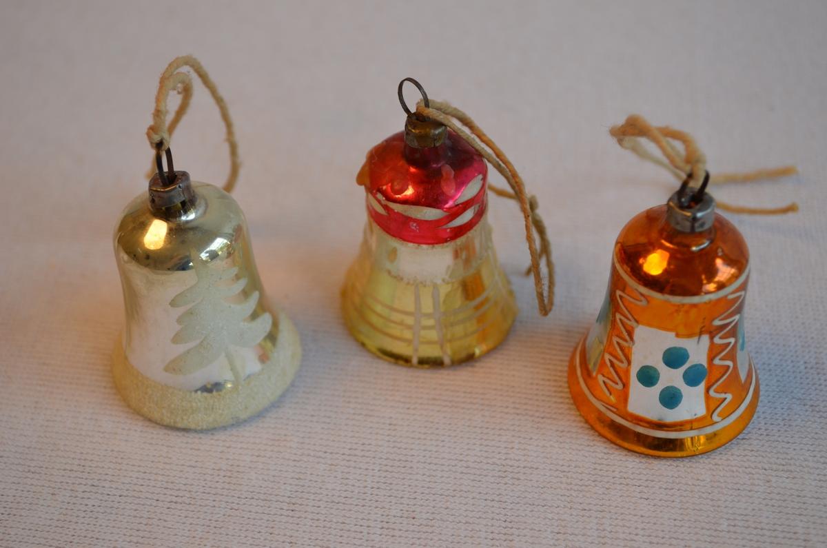 3 juleklokker med ulik farge og mønster. Lik storleik. Klokke 1: Sølvfarga med kvit rand nederst og eit juletre. Klokke 2: Oransje med kvit og blå dekor. 3. Sølv og gullfarga med raud og kvit dekor i topp. Klokke tre har også stearinrestar på seg.
