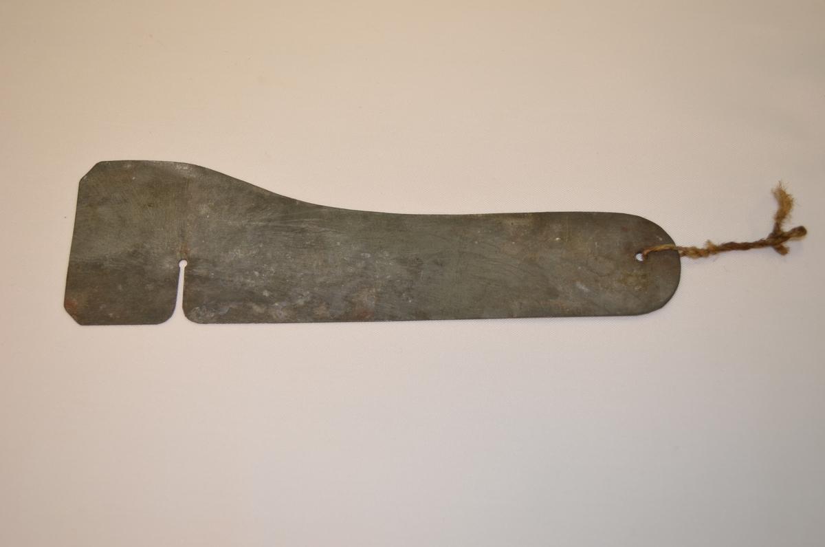 Stålplate som vidar seg ut i eine enden. På den vidaste delen av plata gåtr det eit hakk inn på rundt 2 cm. Ukjent bruk. Denne låg i ei verktøykasse frå ein boktrykkar.