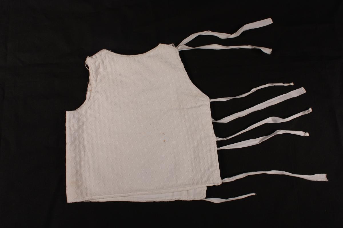 Firkanta med utringingar for hals og armar. Open med tre sett knyteband i eine sida, open på herda  på same sida med eitt sett knyteband
