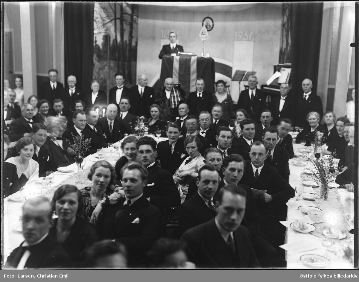 Gruppe menn og kvinner med festpyntet langbord, scene med taler og vimpel, tekst bak: 1836-1936. Ukjent forening