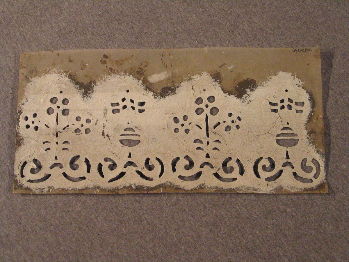 Rektangulært brett med 4 figurar (blomsterfigurar?)2 og 2 like, ordna som to rapportar. Under desse ei løpande rad med 4 figurar,som kanskje skal førestille røter til plantane