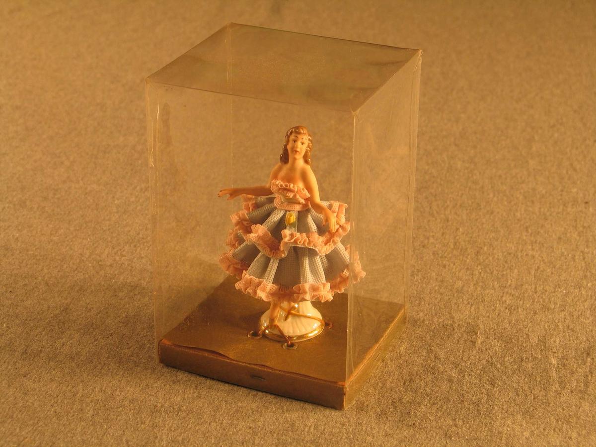 Ballettdanserinne som står fastspent inni ein gjennomsiktig plastboks