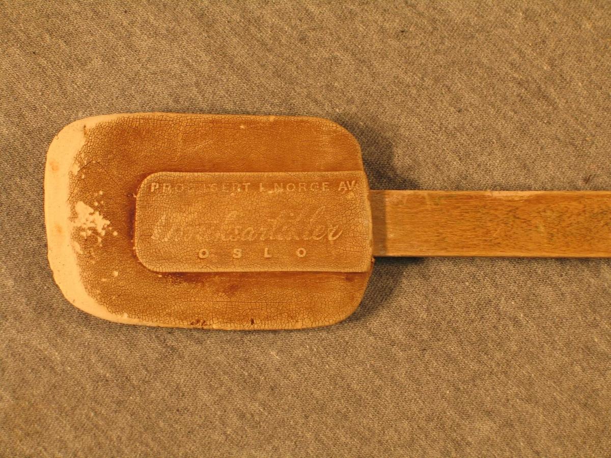 Sleikjepott i gummi sett på eit flatt treskaft