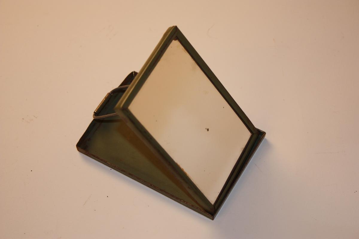 Liten spegel med deksel som kan slåast framfor. Bak er krok til oppheng. dekselet er hengsla slik at spegelen kan stå skrått oppi det.