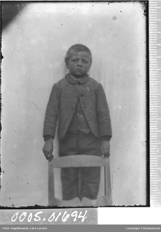 Portrett av en gutt ved en stol.