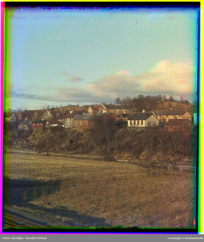 Landskap med jernbanespor og åker i forgrunnen med bebyggelse bak.
