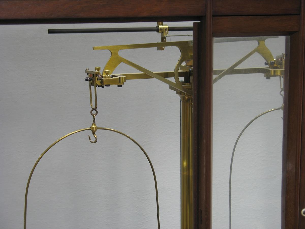 En precisionsvåg i ett skåp med glasväggar och dörrar.